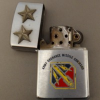 https://chell.lib.fit.edu/plugins/Dropbox/files/Medaris_Physical_Objects/Star-Mounted-Zippo-Lighter-Open.png